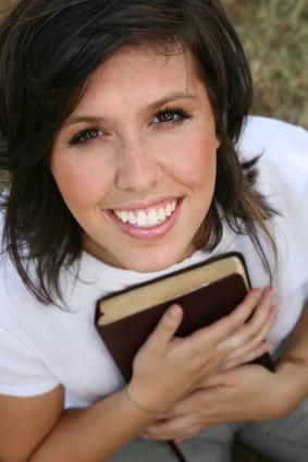 lächelnde Frau, mit einer Bibel in der Hand