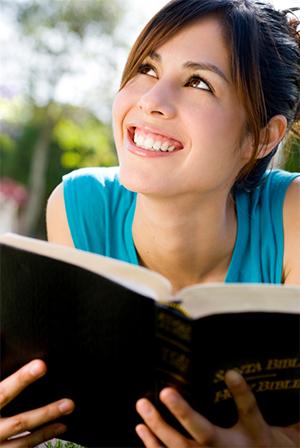 = lächelnde junge Frau, die in der Bibel liest