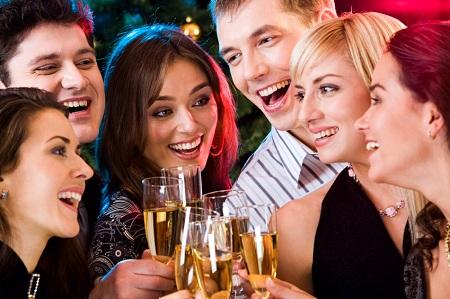 junge Leute stossen auf einer Party miteinander an