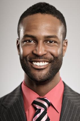 Un homme souriant vêtu d'un costume