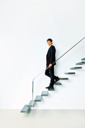 Un homme sur un escalier mural, se tenant à une rambarde
