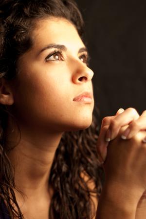Une jeune femme en prière, les mains croisées et les yeux dirigés vers le haut