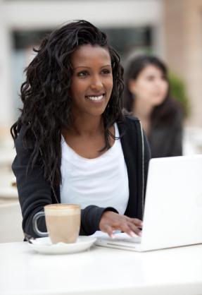 jeune femme souriante qui travaille sur un ordinateur portable