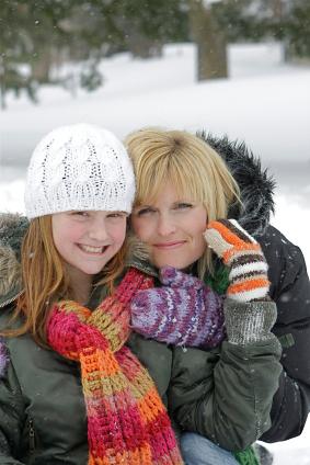 Mère et fille se tenant dans les bras dans une forêt enneigée