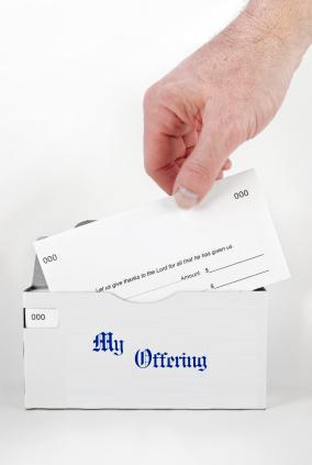 main d'une personne plaçant un papier carton dans une enveloppe d'offrandes