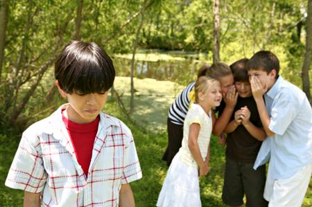 Jeune garçon isolé dont un groupe d'autres jeunes se moque