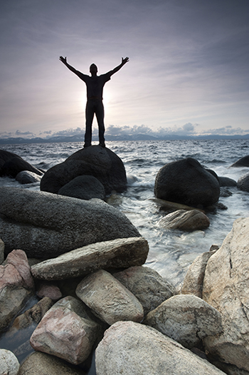 Un homme debout sur un rocher en bord de mer les bras élevés vers le ciel