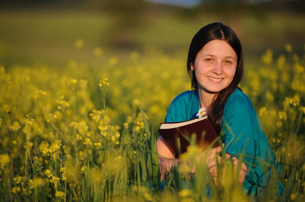 लड़की बाइबल पकड़े फूलों का एक क्षेत्र में बैठी है