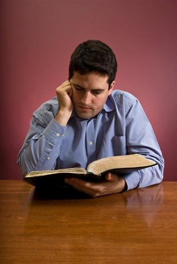 आदमी बाइबल पढ़ रहा है