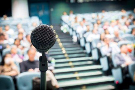 microfon poziționat în fața unei mari mulțimi