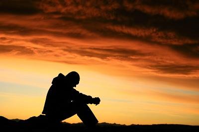 오렌지 빛 하늘을 배경으로 사색하고 있는 남자의 모습