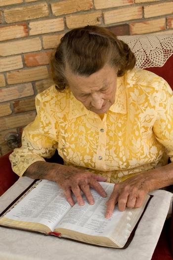 سيدة مسنة تدرس الكتاب المقدس