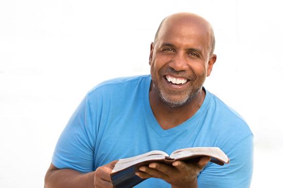 رجل مبتسم يمسك الكتاب المقدس
