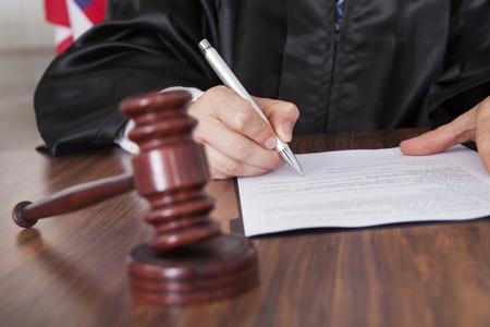 Richter unterschreibt ein Dokument in einem Gerichtssaal