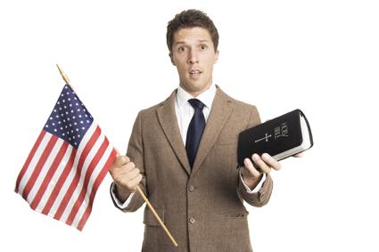 ein Mann hält eine amerikansiche Flagge und eine Bibel
