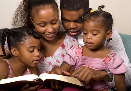 Kinder studieren die Bibel zusammen mit ihren Eltern