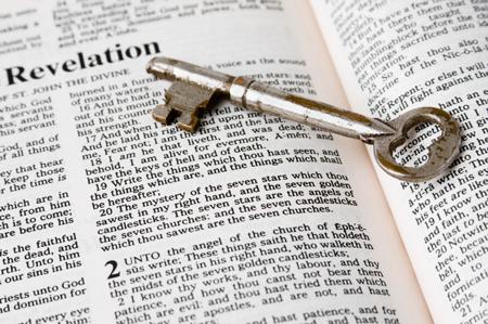 Schlüssel liegt auf einer geöffneten Bibel (das Buch der Offenbarung)