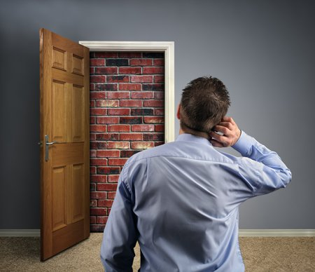 벽돌로 닫힌 출입문을 응시하고 있는 남자