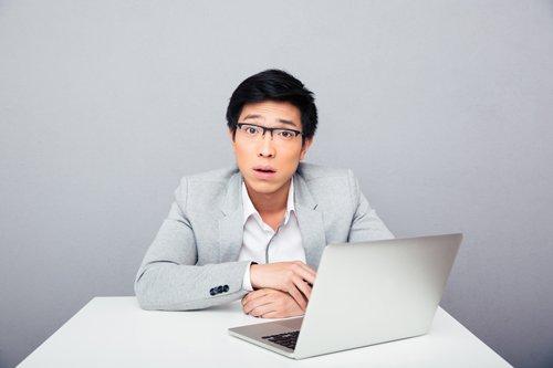 랩탑 컴퓨터 앞에 앉아 있는 놀란 표정의 남자