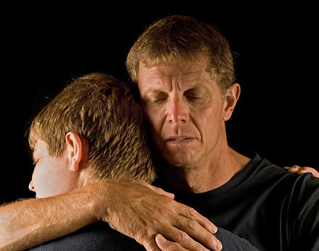 Ein weinender Vater umarmt seinen Sohn