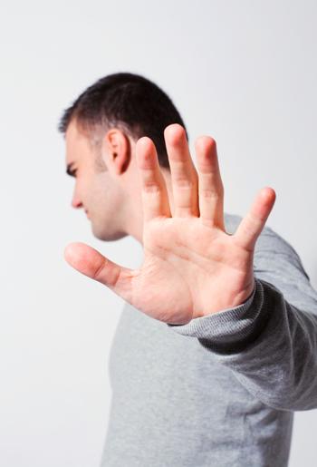 Ein Mann, der nichts hören will und abwehrend seine Hand emporhält