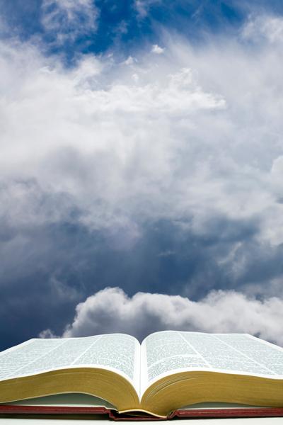 eine geöffnete Bibel, von Wolken umgeben