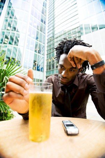 Un homme plongé dans ses pensées, contemplant une boisson alcoolisée (bière), devant un gratte-ciel.