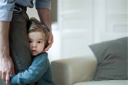 shy child clinging to parent