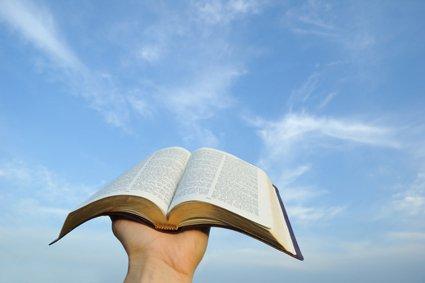 bukas na Bibliya na hawak sa kalangitan