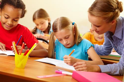 Des enfants dessinant en classe, encadrés par leur maîtresse