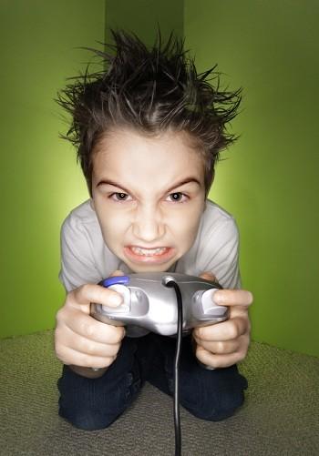 Jeune garçon nerveux, enragé et en colère, jouant à des jeux vidéo, tenant une manette
