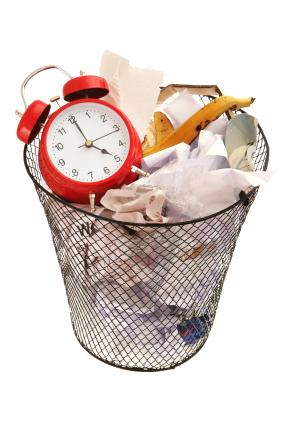horloge réveil mécanique rouge dans une poubelle métallique grillagée pleine d'ordures : déchets de nourriture, peau de banane, et papiers froissés