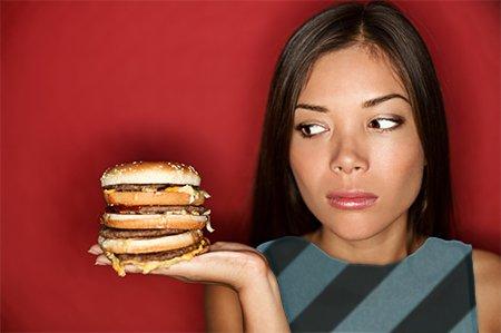 Une fille, jeune femme, tenant un grand hamburger dans sa main, le regardant avec envie, gourmandise ou gloutonnerie.