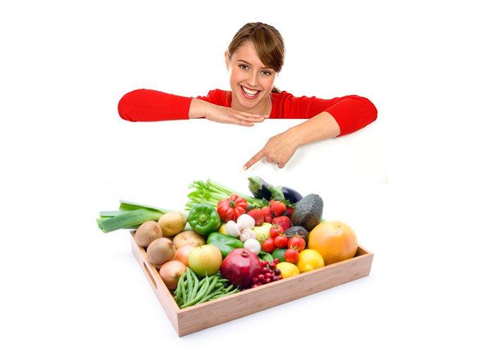 fille, jeune femme souriante pointant vers une boîte de produits frais, fruits et légumes sur un plateau en bois: haricots verts, avocats, poireau, aubergines, céleri branche, poivron rouge et vert, tomates cerises, champignons, pommes de terre, fraises, pommes, pamplemousse, citrons, grenade, baie rouge, cranberries, kiwi.