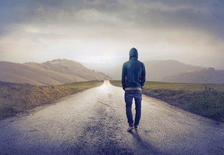 Promenade solitaire, chemin solitaire : homme vu de dos, en jean et gilet à capuche, marchant sur une route déserte, dans un paysage de champs d'herbe verte et de collines, ciel gris, ombragé, avec une lumière diffusant à travers les nuages.