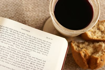 Jus de raisin, pain au levain, et Bible ouverte à l'Évangile de Matthieu, au chapitre 26, versets 21 à 31, symboles de la Nouvelle Alliance en Son sang et en Son corps, notre substitut, commémorée lors de la Sainte Cène.