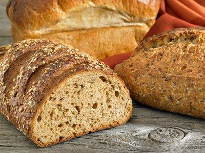 miches de pain complet aux céréales, et pain brioché, sur table en bois, avec nappe (serviette) tissu rouge orangé.