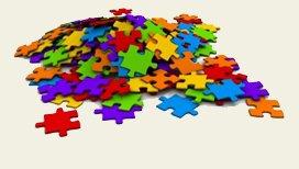 Pièces de puzzle de différentes couleurs (rouge, bleu, violet, orange, vert, jaune) non assemblées, en un grand tas désordonné.