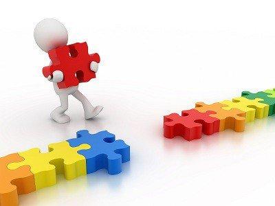 un personnage bonhomme 3D blanc, à la tête sans visage, reliant en ligne les pièces d'un puzzle multicolore : des pièces rouges, oranges, jaunes, vert foncé, vert clair, bleu.