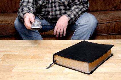 homme assis sur un canapé regardant la télévision, télécommande en main, avec une Bible fermée posée sur la table en face de lui.