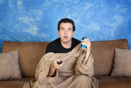 Un homme sous une couverture beige assis devant la télévision, comme hypnotisé devant un film ou une émission, la télécommande dans une main, et une boisson dans l'autre main (canette de bierre ou soda), assis sur un canapé marron.