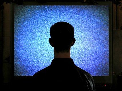 un homme de dos, se tenant stupidement devant un écran plat de télévision.