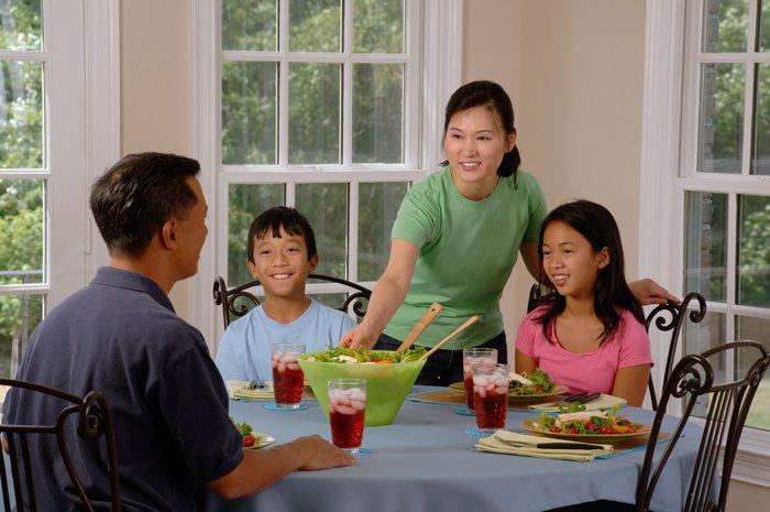 une famille avec deux enfants, à table, en train de déjeuner une salade composée accompagnée de boissons fraîches.