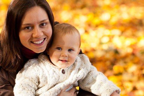 mère célibataire et son bébé, avec un gilet en laine blanc, sur un fond d'automne aux feuilles multicolores.