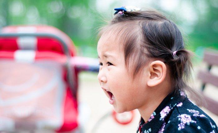colère d'un enfant, une petite fille, en train de crier sur un banc dans un parc