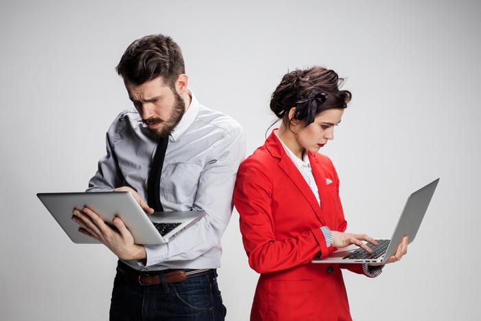 un homme et une femme en tenue d'affaire, debout, tenant chacun un ordinateur portable ouvert à la main, reposant que le bras gauche, semblant chercher avec concentration et angoisse en tapant de la main droite sur le clavier, tête baissée, font plissé.