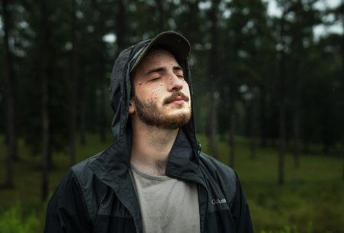 Jeune homme sous la pluie, en veste ouverte imperméable noire à capuche, casquette à visière, les yeux fermés, tête inclinée vers le ciel, le visage barbu offert à la pluie, dans un environnement boisé, clairière entourée d'une forêt.