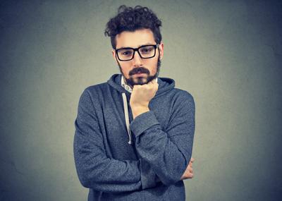 jeune homme à l'air pensif, barbe et lunettes noires, cheveux bouclés mi-courts, sweat décontracté couleur chiné à capuche et ficelle blanche, bras semi-croisés, la main (le poing) sous le menton.