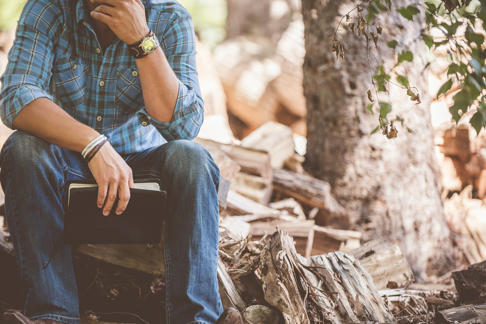 man sitting in the woods, holding a Bible