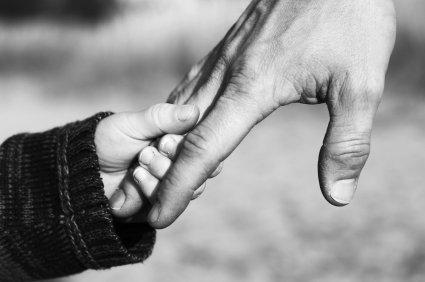 أب يمسك يد طفله